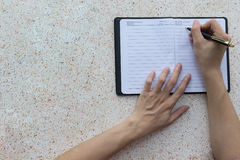 Сочинительство руки взгляд сверху на тетради Стоковые Изображения RF