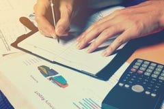 Сочинительство руки женщины делает примечание и высчитывает офис финансов дома Стоковые Изображения RF