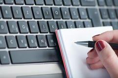 Сочинительство руки женщины на тетради чистого листа бумаги с компьтер-книжкой в офисе Стоковая Фотография RF