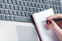 Сочинительство руки женщины на тетради чистого листа бумаги с компьтер-книжкой в офисе Стоковые Фотографии RF
