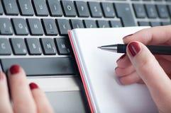Сочинительство руки женщины на тетради чистого листа бумаги с компьтер-книжкой в офисе Стоковые Изображения