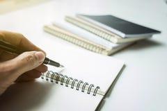 Сочинительство руки конца-вверх человеческое что-то на бумажной тетради в sunli Стоковая Фотография RF
