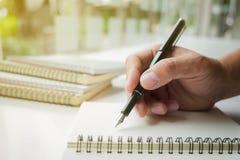 Сочинительство руки конца-вверх человеческое что-то на бумажной тетради в sunli стоковое фото rf