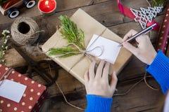 Сочинительство руки на подарках на рождество Стоковая Фотография