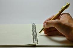 Сочинительство руки на тетради Стоковая Фотография RF