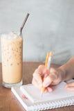 Сочинительство руки на notepaper на кофейне Стоковые Фото