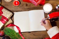 Сочинительство руки Санты на книге рождества Стоковое фото RF