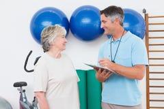 Сочинительство тренера на доске сзажимом для бумаги с старшей женщиной Стоковые Изображения