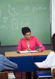 Сочинительство учителя в связывателе на столе с студентами внутри Стоковое Изображение