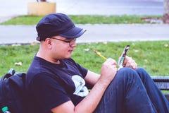Сочинительство человека в парке Стоковая Фотография