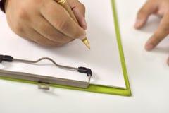 Сочинительство человека на чистом листе бумаги на доске сзажимом для бумаги Стоковые Фотографии RF