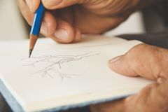 Сочинительство человека на sketchbook стоковое изображение