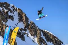 Сочи, Россия - 25-ое марта 2014: Snowboarder летает в воздух от большой скачки воздуха на предпосылке голубого неба и горы стоковая фотография