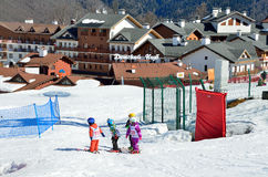 Сочи, Россия, 29-ое февраля 2016, маленькие ребеята катаясь на лыжах на предпосылке здания ребенка бьет на лыжном курорте Розе Kh Стоковое фото RF
