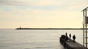 Сочи, Россия, 23-ье апреля 2019 - заход солнца на Чёрном море, силуэты рыболовов на волнорезах видеоматериал