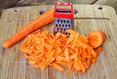 Сочная заскрежетанная морковь на деревянной разделочной доске Необыкновенные тайна и обман зрения стоковые изображения rf