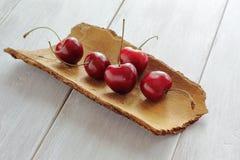 Сочная красная вишня на расшиве сосны Деревянный countertop стоковое изображение