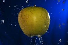 Сочное желтое яблоко с водой падает на голубую предпосылку Стоковое Изображение