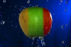 Сочное зеленое желтое красное яблоко с водой падает на голубую предпосылку Стоковая Фотография RF
