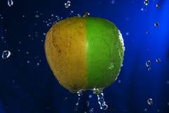 Сочное зеленое желтое яблоко с водой падает на голубую предпосылку Стоковая Фотография