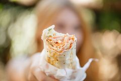 Сочное shawarma в руках девушки на пикнике Стоковое Фото