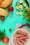 Сочные зажаренные сосиски, свежие овощи, зеленые цвета и кудрявые плюшки на яркой предпосылке Стоковые Изображения RF
