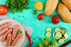 Сочные зажаренные сосиски, свежие овощи, зеленые цвета и кудрявые плюшки на яркой предпосылке Стоковое Изображение