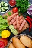 Сочные зажаренные сосиски, соусы, свежие овощи, кудрявые плюшки, на деревянной предпосылке Стоковые Фото