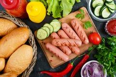 Сочные зажаренные сосиски, соусы, свежие овощи, кудрявые плюшки, на деревянной предпосылке Стоковое Изображение RF