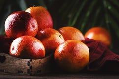 Сочные зрелые сияющие красные кровопролитные апельсины в подносе для делать освежая коктейль на деревенской предпосылке деревянно стоковые фотографии rf