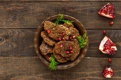 Сочные котлеты печени с семенами гранатового дерева на керамической плите на темной деревянной предпосылке Стоковые Фото