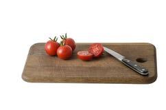 Сочные органические томаты вишни на изолированной разделочной доске Стоковая Фотография