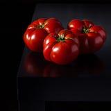 Сочные томаты на деревянной темной предпосылке Стоковые Фотографии RF