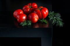 Сочные томаты с dropletson укропа и воды деревянная темная предпосылка Стоковое Фото