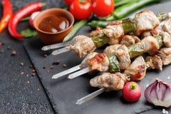 Сочные kebabs от свинины на протыкальниках Мясо сваренное на открытом огне и свежих овощах на черной предпосылке 1 жизнь все еще Стоковое Изображение RF