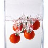 Сочный малый томат вишни упал в воду на белизне Стоковая Фотография RF