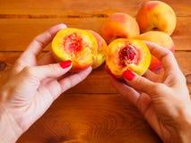 Сочный персик в руках женщины Стоковые Фото