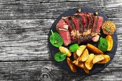 Сочный стейк говядины глаза нервюры с зажаренной картошкой заклинивает Стоковое Изображение RF