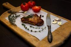 Сочный стейк говядины на деревянной старой разделочной доске с специями и овощами На черной предпосылке для дизайна текста для Стоковое Изображение