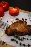 Сочный стейк говядины на деревянной старой разделочной доске с специями и овощами На черной предпосылке для дизайна текста для Стоковая Фотография RF