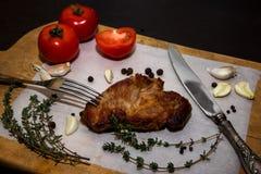 Сочный стейк говядины на деревянной старой разделочной доске с специями и овощами На черной предпосылке для дизайна текста для Стоковые Фото