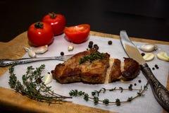 Сочный стейк говядины на деревянной старой разделочной доске с специями и овощами На черной предпосылке для дизайна текста для Стоковое фото RF