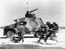 Солдаты бежать вдоль стороны танка в пустыне Стоковые Фотографии RF