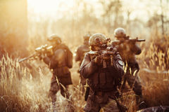 Солдаты с оружи на поле стоковые изображения rf