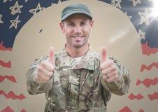 Солдат давая 2 большого пальца руки вверх против флага нарисованного рукой американского с пирофакелом Стоковые Изображения RF