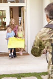 Солдат возвращающ домой и приветствованный семьей стоковые фото
