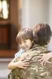 Солдат возвращающ домой и приветствованный сыном стоковое фото