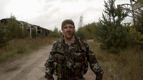 Солдат идя на грязную улицу окруженную покинутыми зданиями видеоматериал