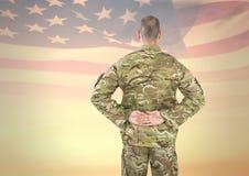 Солдат от задней части с руками на задней части против американского флага Стоковое Изображение