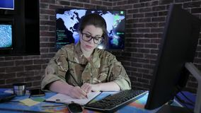 Солдат портрета девушки в стеклах и форме, работая с видеоматериал